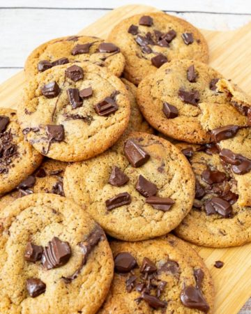 Chewy chocolate chip cookies on a wooden board.