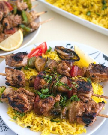 A plate with yellow rice and chicken on skewers.