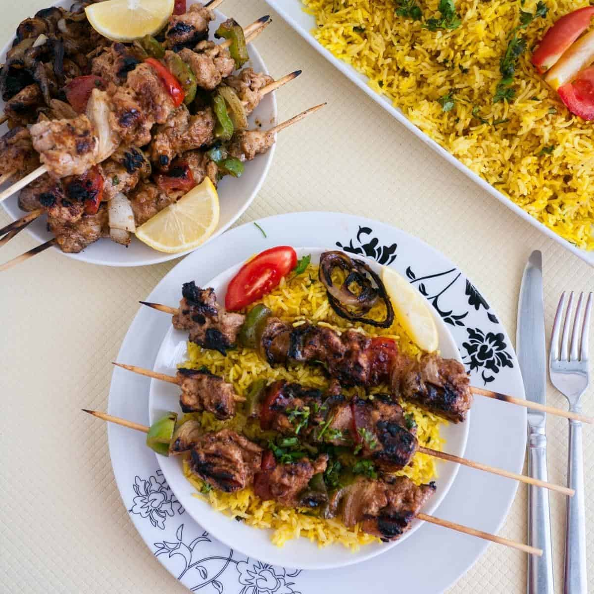 Grilled chicken on skewers over turmeric rice.
