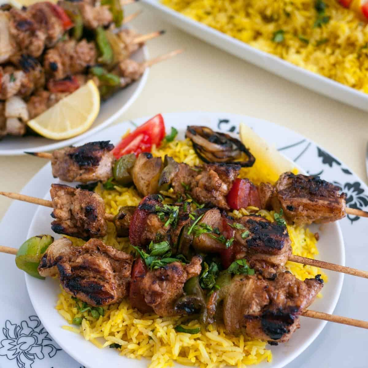 Grilled chicken skewers on a bed of yellow rice.