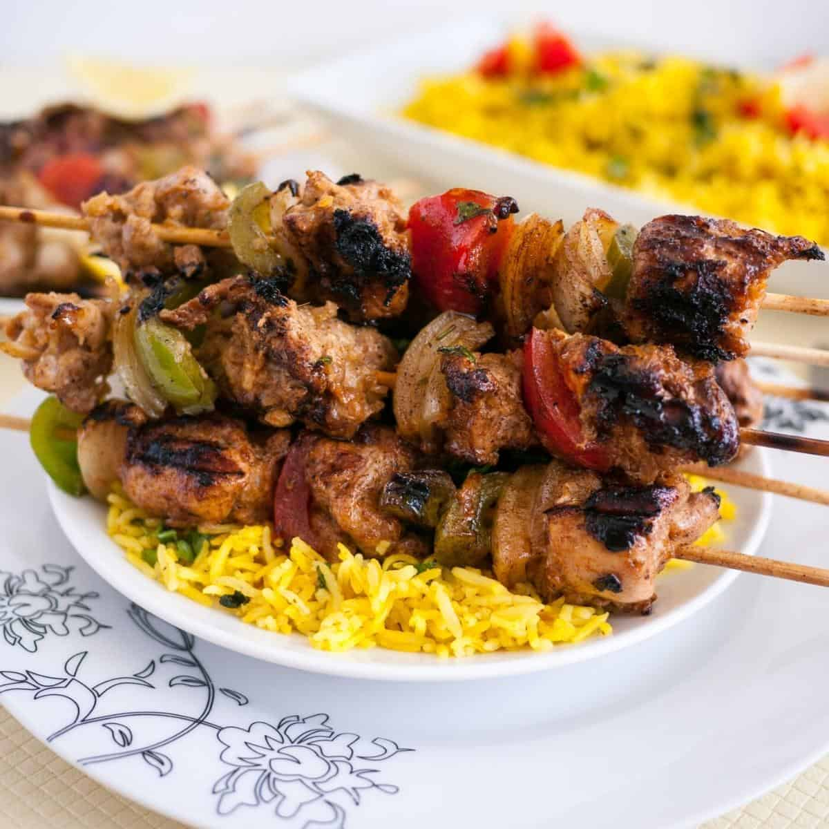 A plate with rice and chicken and veggies on skewers.