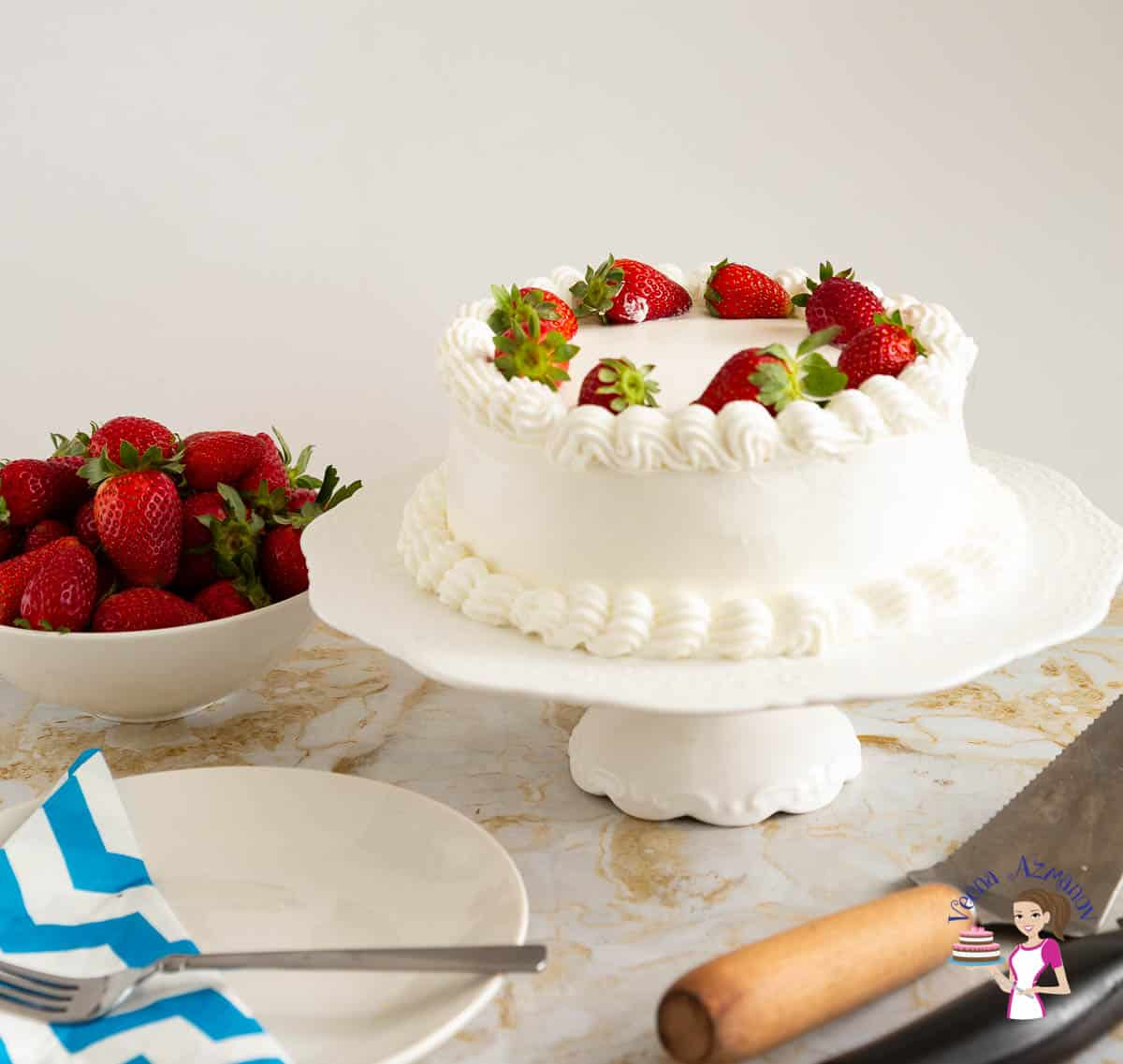 A frosted cake with whipped cream and strawberries