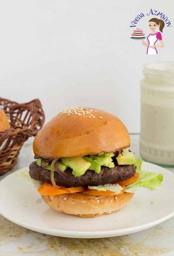 A plated kebab style beef hamburger with tomatoes, grilled onions, avocado and tahini sauce.