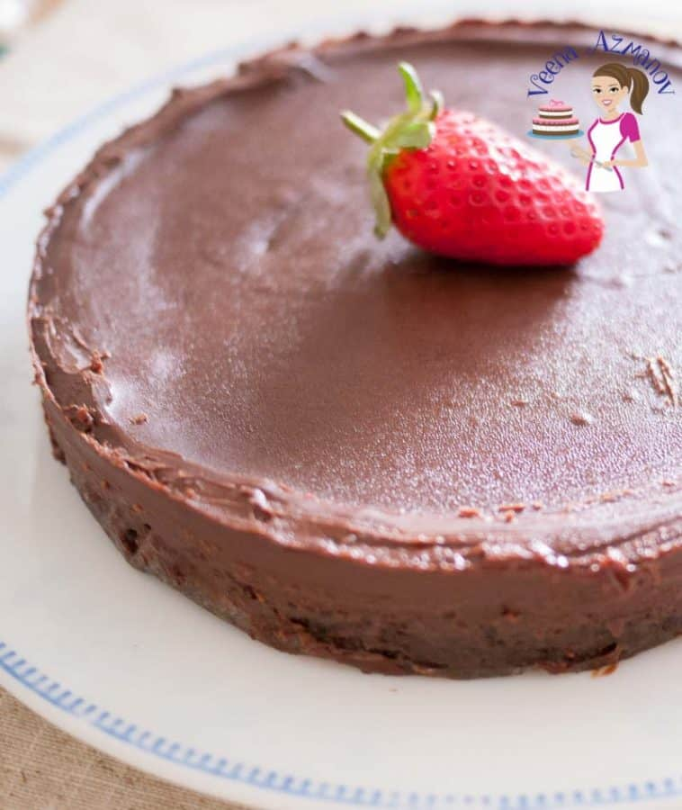 A close up of a chocolate cake with a strawberry on top.
