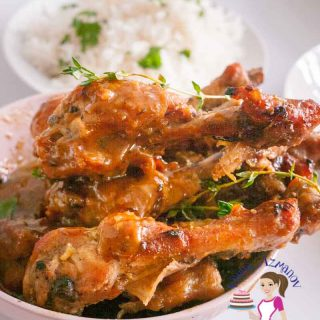 A bowl with baked chicken legs with honey and mustard.