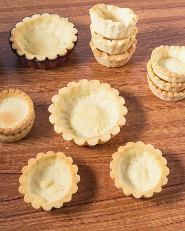 Pastry shells for mini tarts on a table.