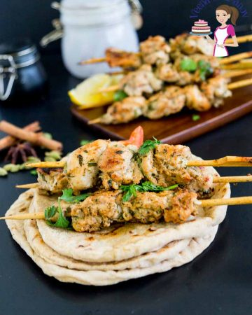 chicken skewers on a stack of pita bread.