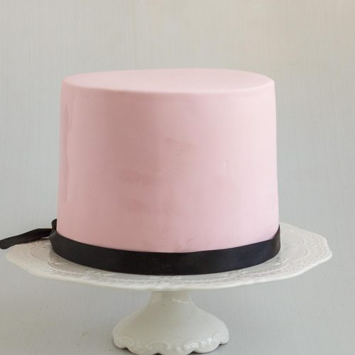 A pink cake covered in fondant