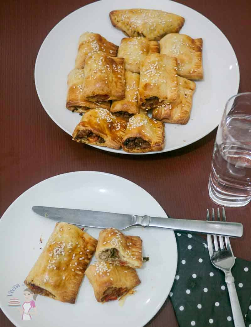 A top view of these meat stuff puff pastry in a plate. Once cut to show the inside meat stuffing.