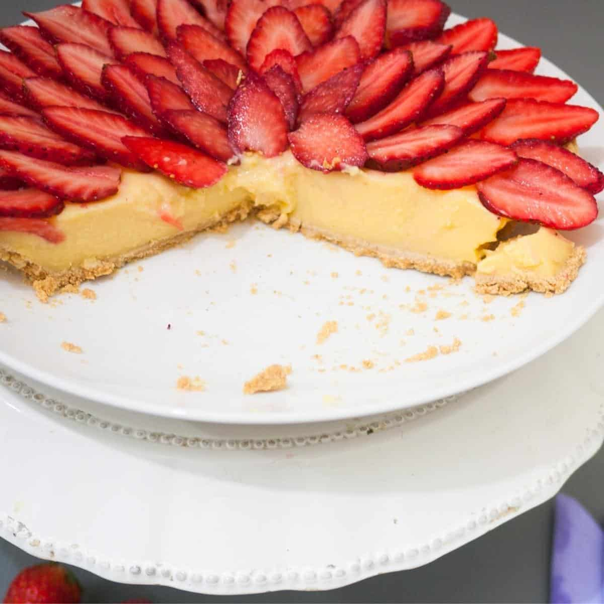 A cut fruit tart on a plate and cake stand