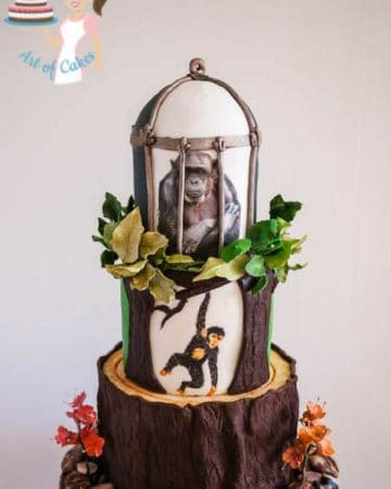 A cake decorated to look like a chimpanzee on a tree and in a cage.