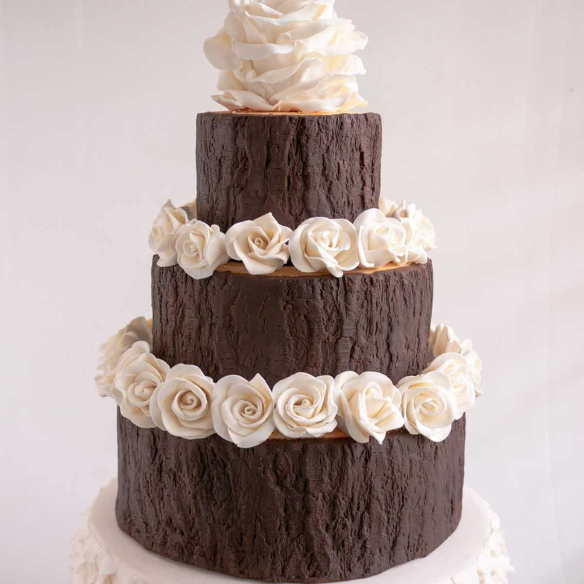 A three tier cake frosted with modeling chocolate.