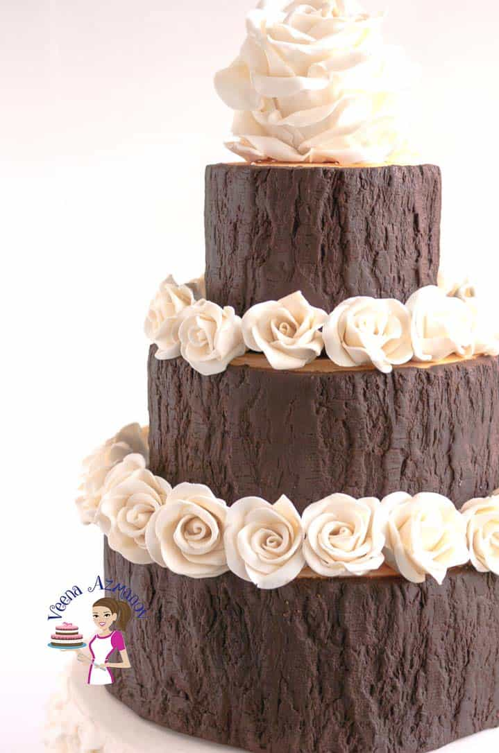 White modeling chocolate roses on a decorated cake.