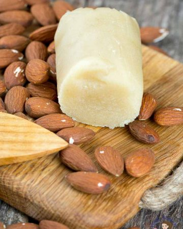 A piece of marzipan and scattered almonds on a wooden board.