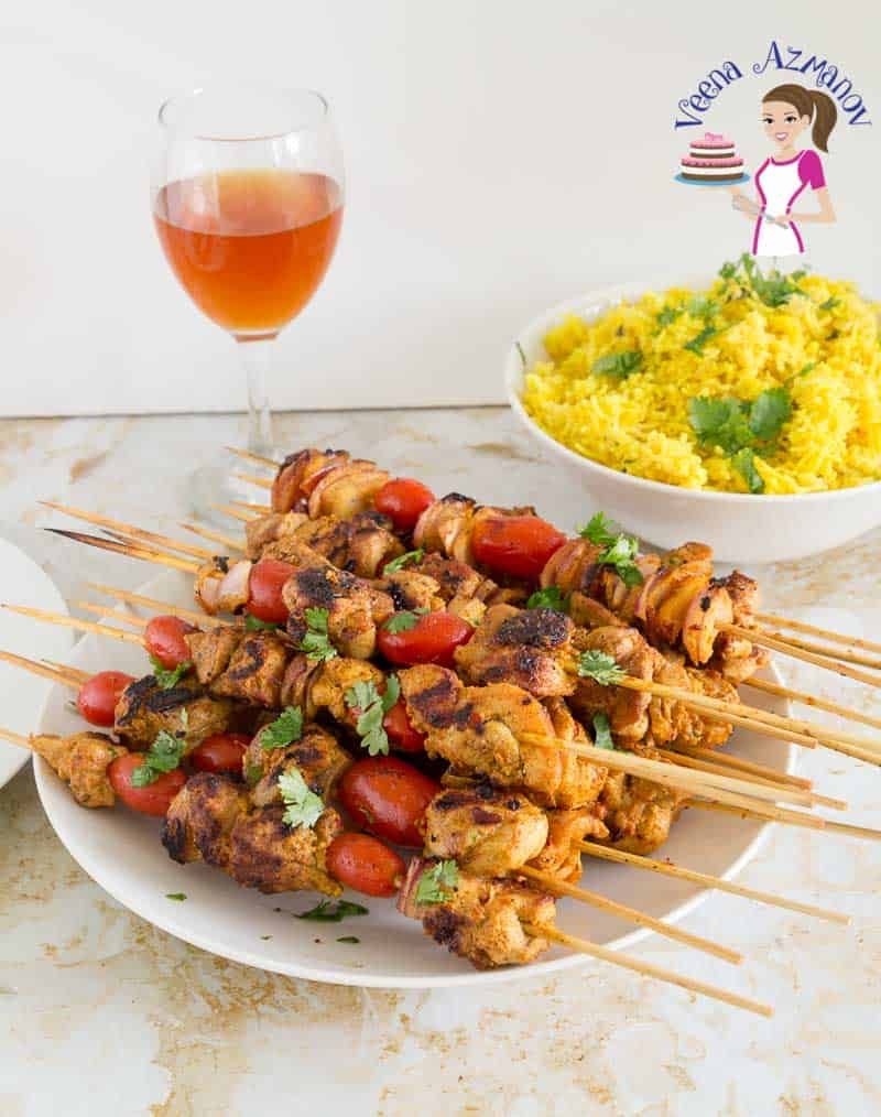 A platter of Chicken on skewer or kebabs served with Turmeric rice and a glass of homemade wine.