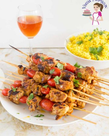 Chicken skewers stacked on a plate.