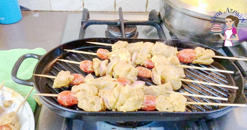 A platter of Chicken on skewer or kebobs served with Turmeric rice and a glass of homemade wine.