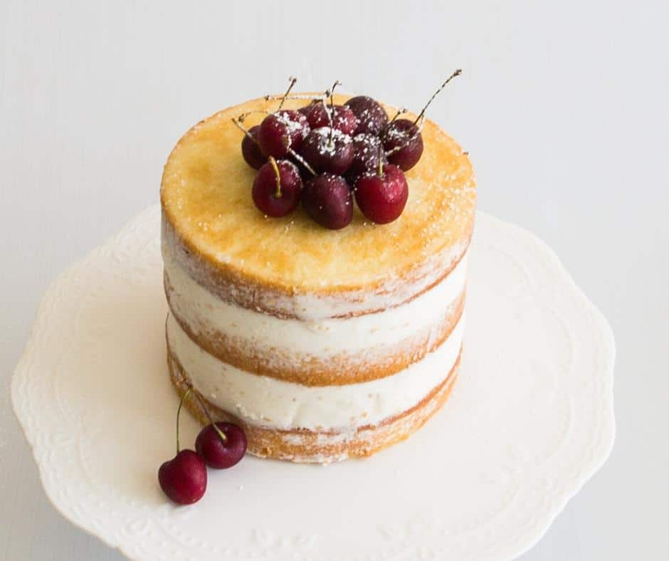 A vanilla layer cake with cherries on top.