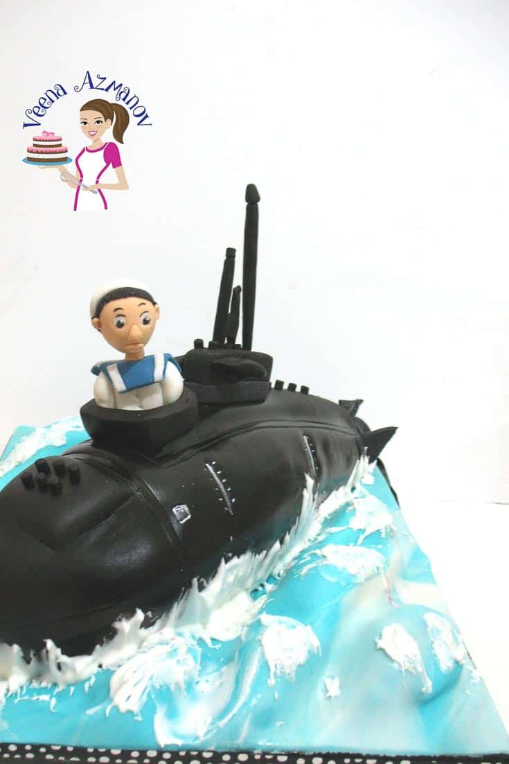 A Submarine cake with water and waves using marble fondant to look like water using white and blue fondant