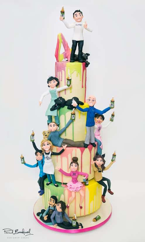 A cake decorated with figurines of people.