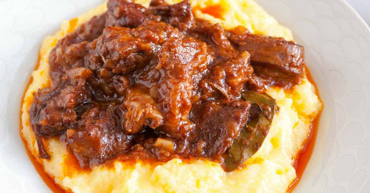An absolute comfort food perfect anytime of the year. This slow cooked lamb with creamy polenta has everything you look for in comfort food. Meat cooked to fork tender in a tomato sauce and smoked spices. Served over a bed of creamy Parmesan flavored polenta for that ultimate luxury.
