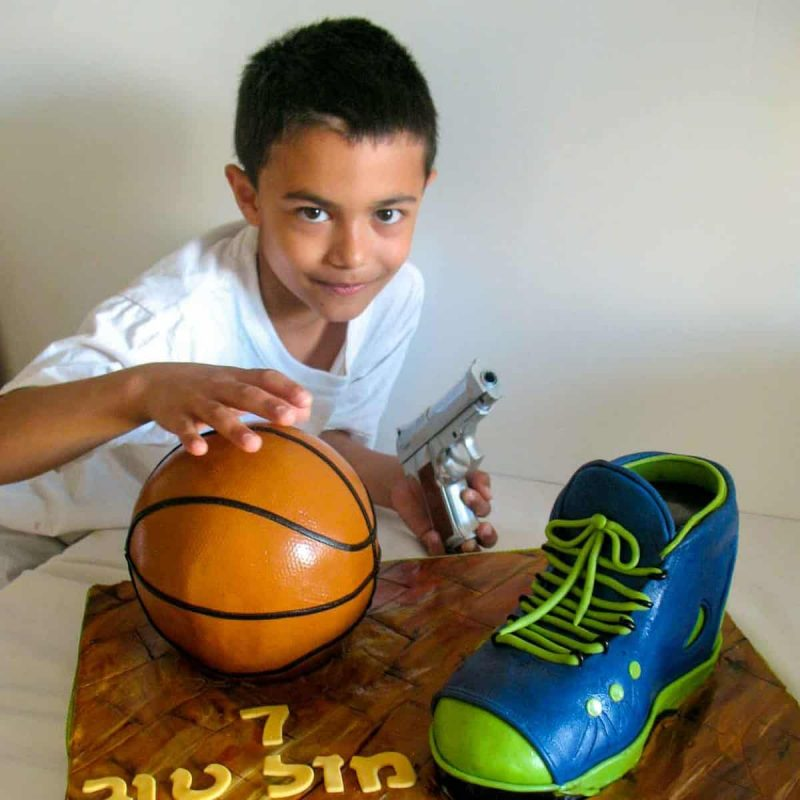A boy next to a cake decorated like a basketball and a shoe.