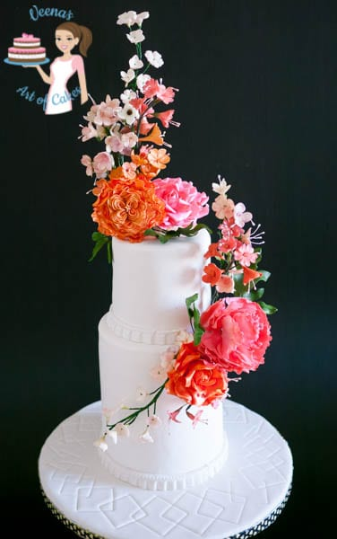 A wedding cake decorated with sugar flowers.
