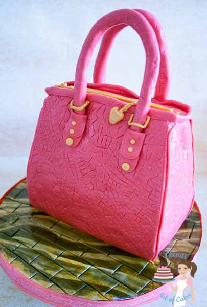 A cake sculpted to look like a pink handbag.