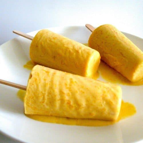 Three mango kulfi pops on a plate.