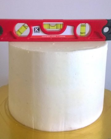 A buttercream frosted cake with a leveler.