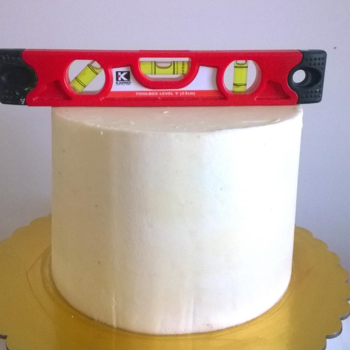 A buttercream frosted cake with a cake leveler.