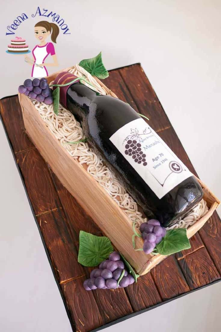 A cake sculpted to look like a wine bottle in a wooden box.