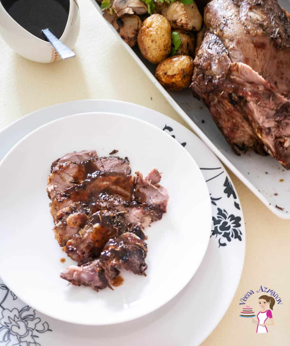 A plate with a piece of roast leg of lamb.