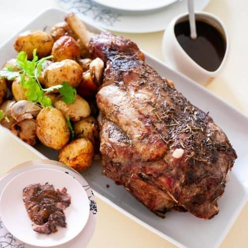 A white platter with a leg of lamb and potatoes