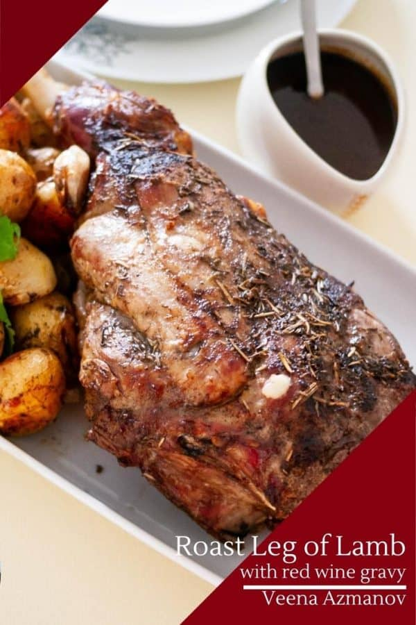A roast leg of lamb with baked potatoes on a serving dish.