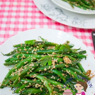 A plate of green beans with sesame seeds.