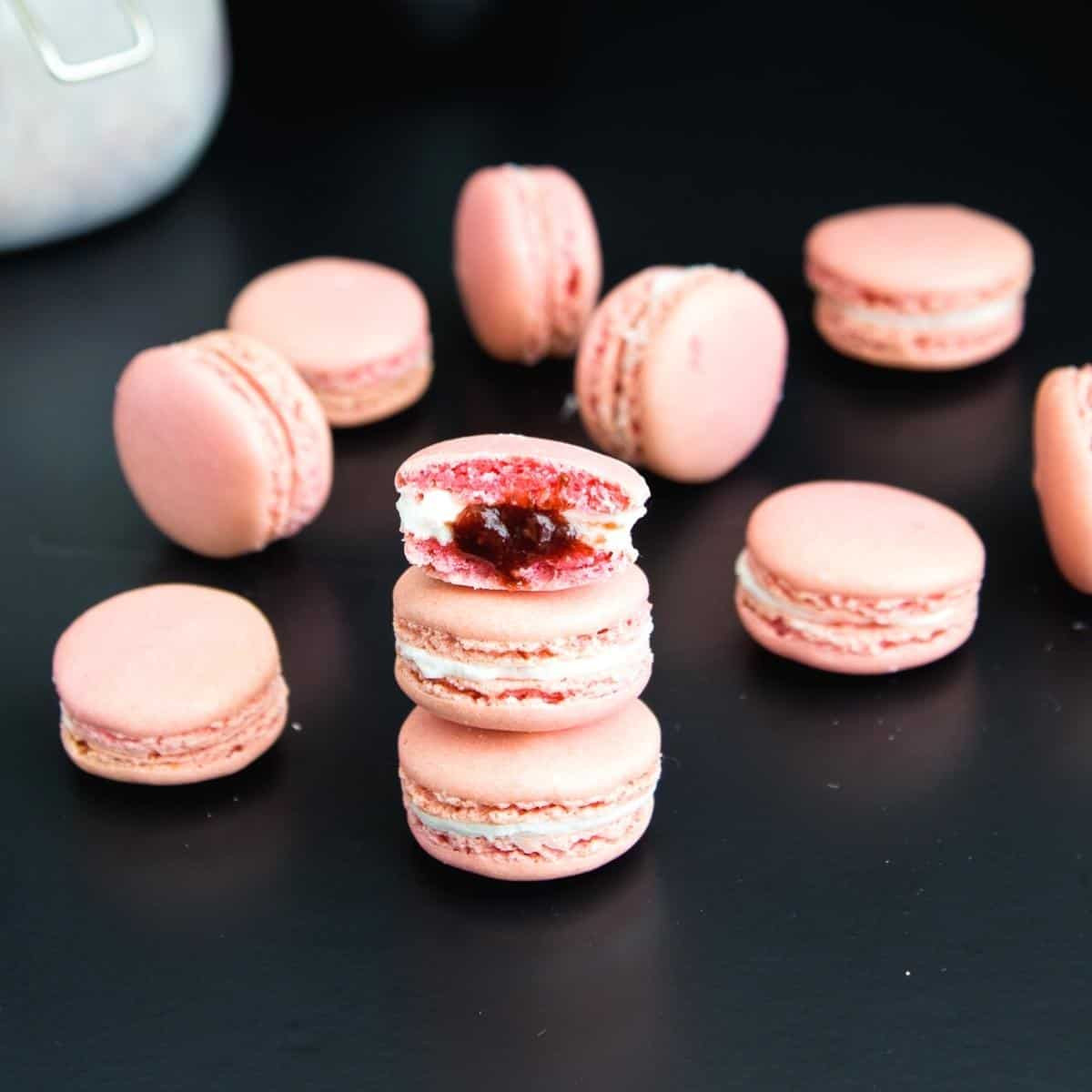 Stack on pink macarons on a black board