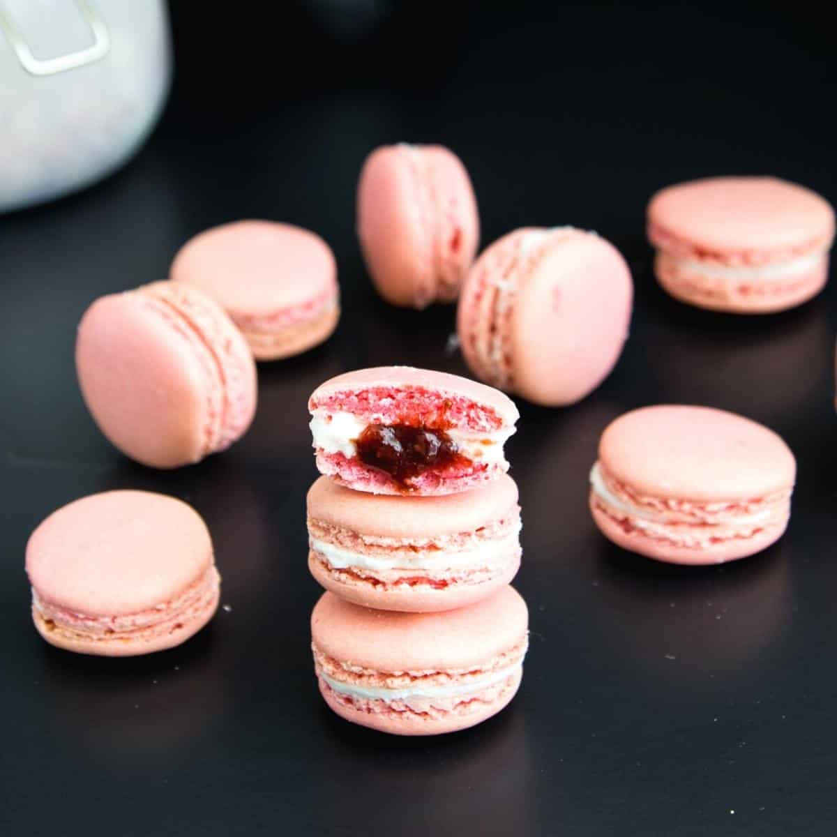 stack of pink macarons on a black board
