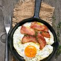 A skillet with sunny side up egg and bacon.