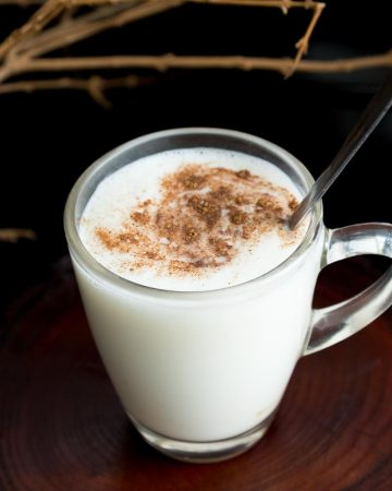 A glass cup with eggnog sprinkled with cinnamon