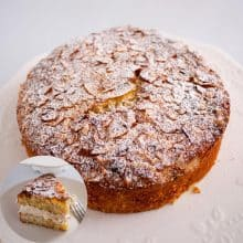 A coconut cake on a table dusted with powdered sugar.