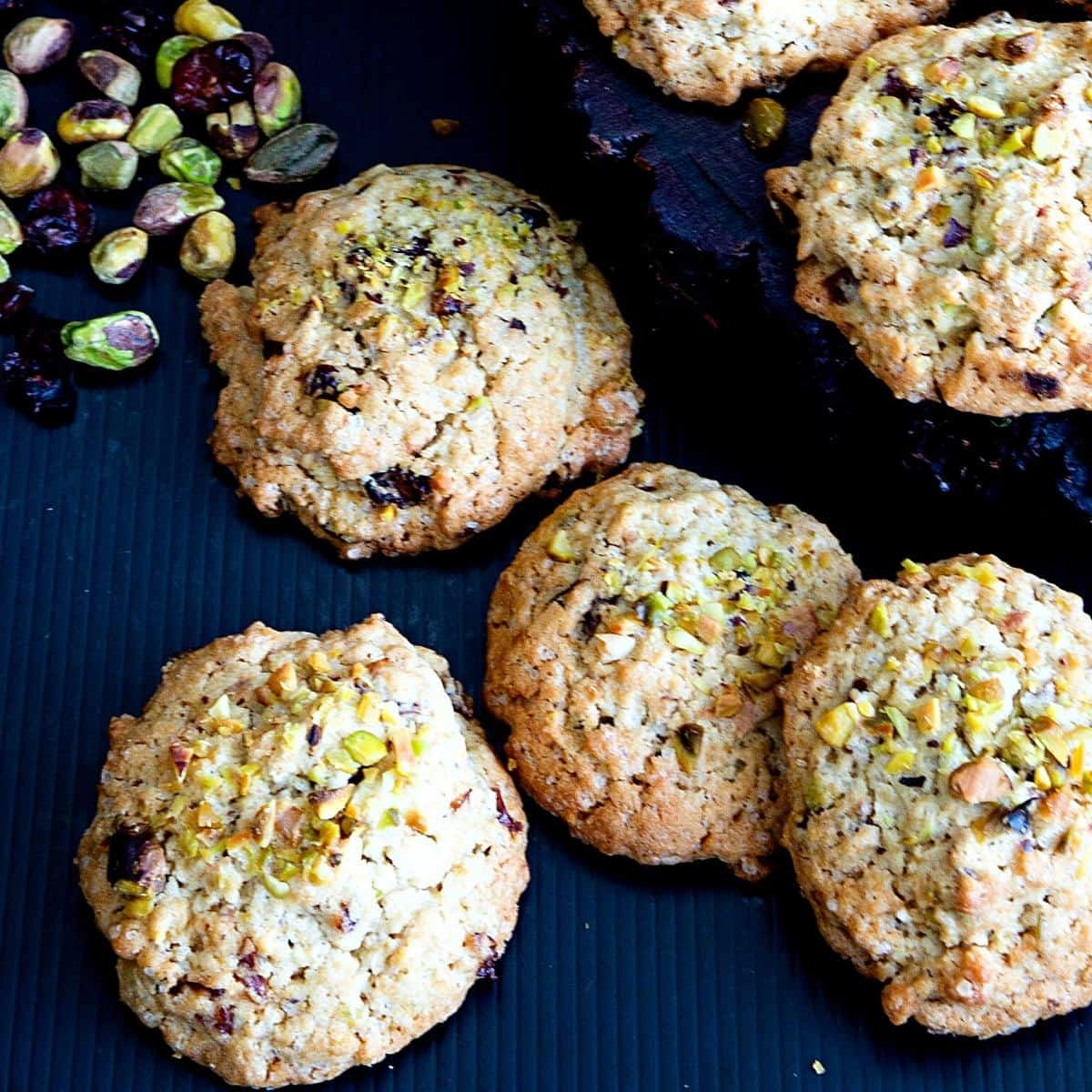 Cookies on a table with some pistachios and cranberries.