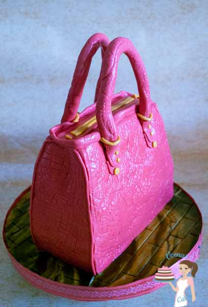 Pink Hand Bag Cake - A Hand bag cake is a perfect cake to make for a lady of any age. Depending on the age you can tweak the colors, accessories and style. Great Tutorial by Veena Azmanov of Veena's Art of Cakes