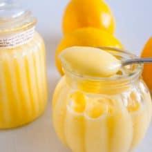 Fresh lemons and jars of fruit curd.