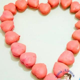 Heart-shaped macarons arranged in a heart shaped manner on a table.