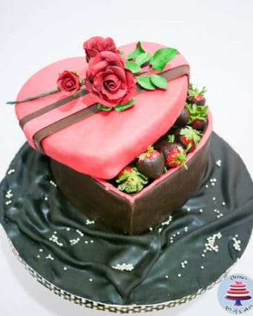 A cake decorated to look like a heart-shaped box of strawberries coated with chocolate.
