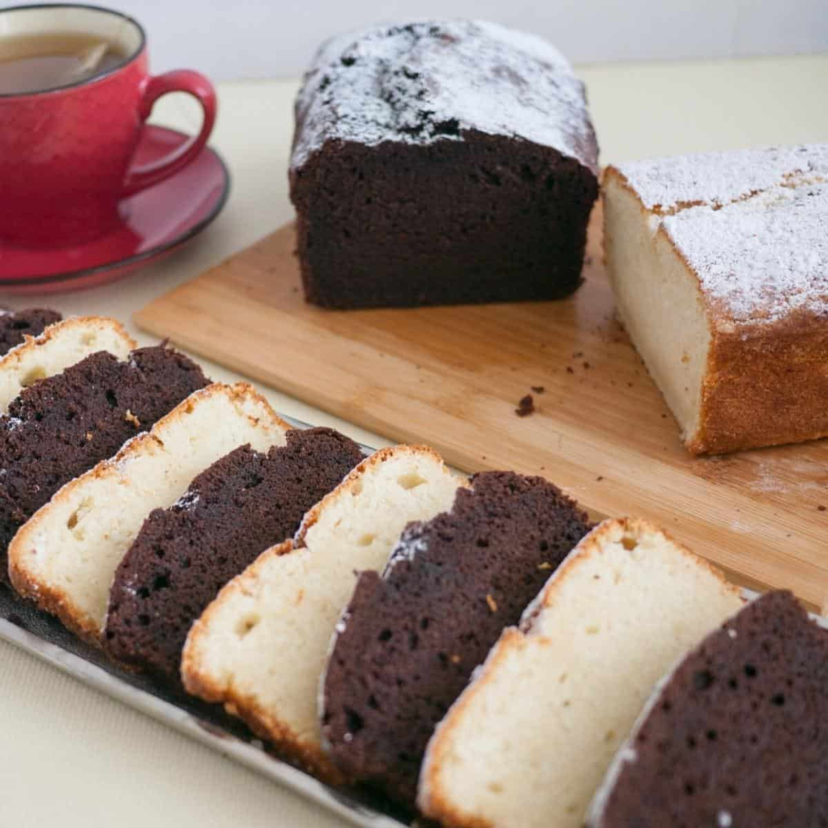 Slices of chocolate and vanilla pound cake on a wooden board.
