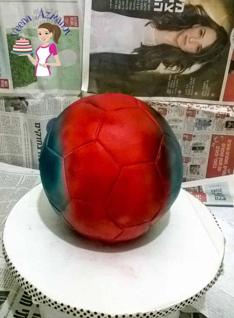 Progress photos of making a cake decorated to look like a Barcelona football.