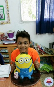 A boy with a cake decorated to look like a minion.