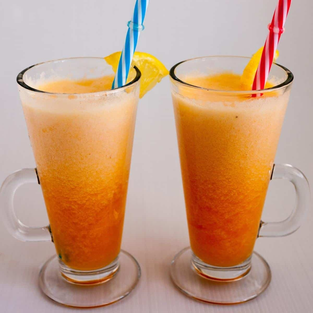 Two glasses with smoothies and straws